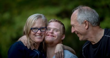 Parents Hugging Son with Downs-